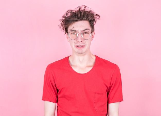 Portret van ontevreden, boos man fronst gezicht als gaan huilen, geïsoleerd op roze studio achtergrond.