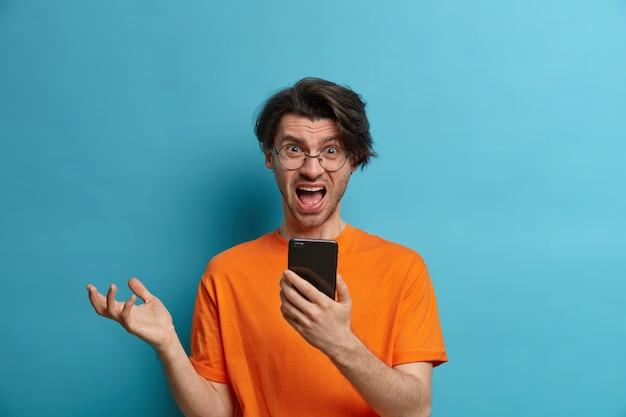 Portret van ontevreden, boze volwassen man heeft een verbaasde reactie bij het lezen van negatief nieuws via mobiel, roept en gebaren, houdt mobiele telefoon vast, draagt vrijetijdskleding, poseert tegen blauwe muur