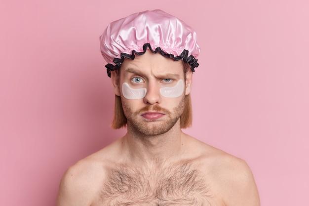 Portret van ontevreden europese man trekt wenkbrauwen op met knorrige uitdrukking past collageenpleisters onder de ogen toe
