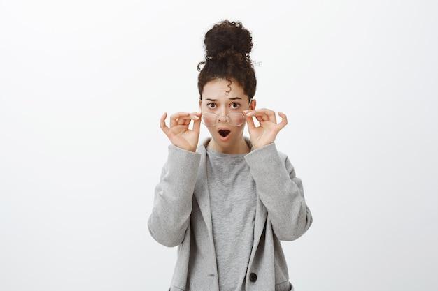 Portret van ontevreden geschokt mooi kaukasisch meisje met krullend haar in glazen en grijze vacht, hand in hand op rand en kaak laten vallen, hijgend van verbazing en verbazing