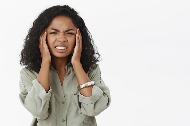 Portret van ontevreden intense afro-amerikaanse jonge vrouw met krullend haar fronsen balde tanden van pijnlijk gevoel tempels aanraken