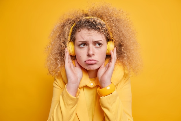 Portret van ontevreden jonge europese vrouw met krullend haar houdt de handen op de koptelefoon heeft gefrustreerde gezichtsuitdrukking, portemonnees lippen