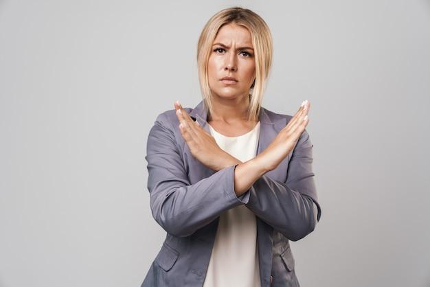 Portret van ontevreden jonge mooie vrouw poseren geïsoleerd over grijze muur stop gebaar maken