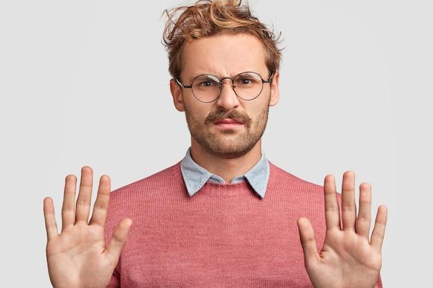 Portret van ontevreden jongeman met knorrige uitdrukking, stop-symbool maakt, handpalmen naar voren houdt, heeft een negatieve gezichtsuitdrukking