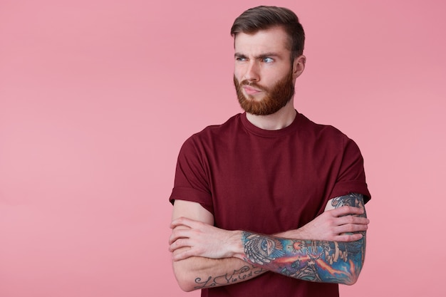 Portret van ontevreden mooie jonge man met gemberbaard en getatoeëerde hand, hand in hand gekruist, frons en wegkijken geïsoleerd op roze achtergrond. mensen en emotie concept.