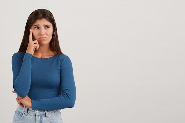 Portret van ontevreden, ongelukkig meisje met donker lang haar, gekleed in een blauwe trui en een spijkerbroek