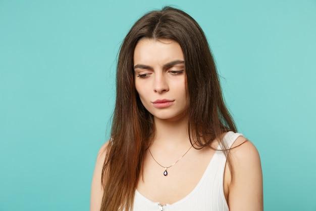 Portret van ontevreden overstuur jonge vrouw in lichte casual kleding opzij kijken naar beneden geïsoleerd op blauwe turquoise muur achtergrond in studio. mensen oprechte emoties levensstijl concept. bespotten kopie ruimte.