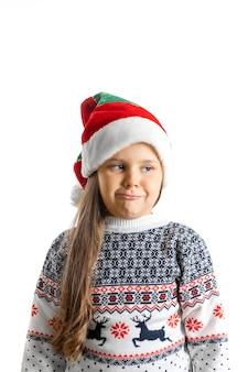 Portret van ontevreden teleurgesteld meisje in witte gebreide kersttrui met rendieren en dwerg...