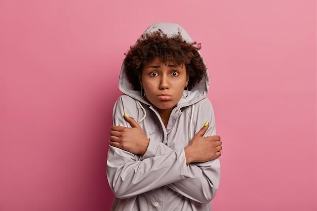 Portret van ontevreden vrouw kruist handen over lichaam, voelt ijskoud na het lopen tijdens nat weer, poseert over roze muur, heeft een boos expressie, kijkt naar horrorfilm, ziet onverwachte scène