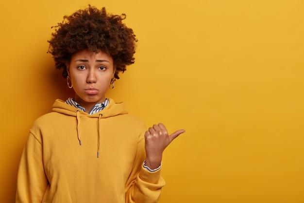 Portret van ontevreden vrouw met donkere huid wijst weg met duim, geeft negatieve feedback, reageert op iets teleurstellend, klaagt en jankt, draagt casual hoodie, geïsoleerd op gele muur