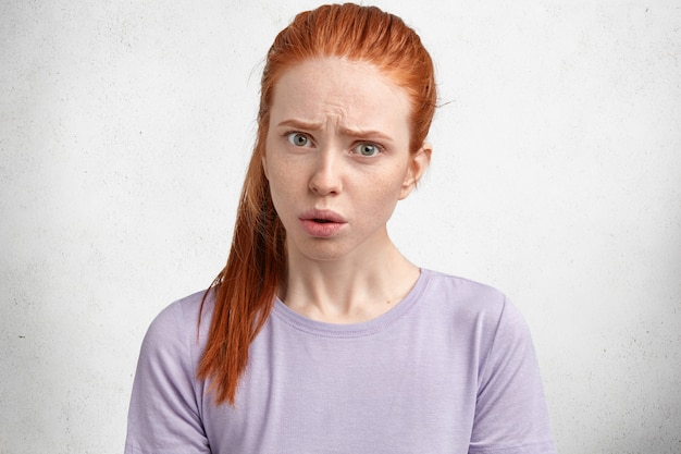 Portret van ontevredenheid mooi vrouwelijk model heeft roodachtig haar, kijkt met ontevreden verbaasde uitdrukking, ontevredenheid hoort iets.