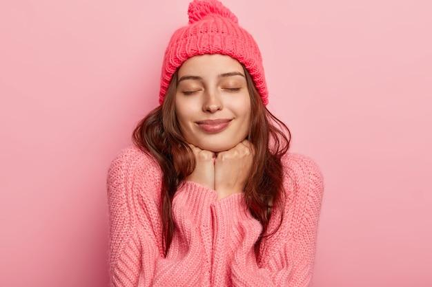 Portret van ontspannen jong vrouwelijk model houdt beide handen onder de kin, heeft de ogen dicht, draagt een roze hoed en trui, voelt zich tevreden, vormt tegen roze achtergrond.