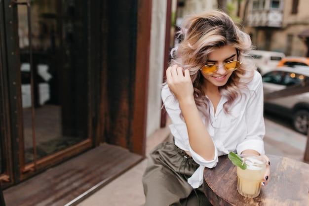 Portret van ontspannen jonge vrouw in wit overhemd en beige rok speelt met haar blonde haren en geniet van koude cappuccino