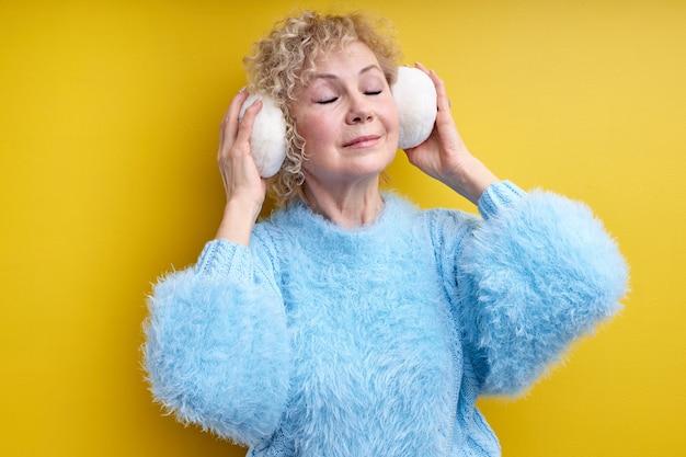 Portret van ontspannen senior vrouw luisteren naar muziek met een koptelefoon, genieten van muziek met gesloten ogen
