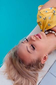 Portret van ontspannende rustige vrouw in gele zomerjurk ligt aan de rand van het blauwe zwembad trendy zeeschelp ketting dragen