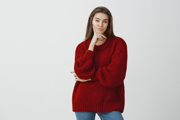 Portret van onverschillige, niet onder de indruk aantrekkelijke vrouwelijke europese vrouw in stijlvolle losse trui, met vingers op de wang en kijkend met ontevreden uitdrukking, minachtend