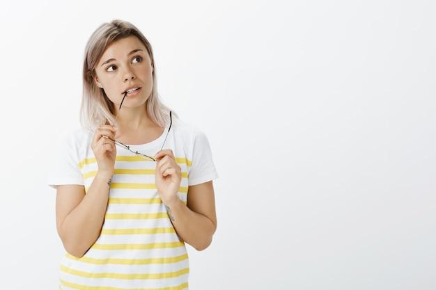 Portret van onzeker blond meisje met een bril poseren in de studio