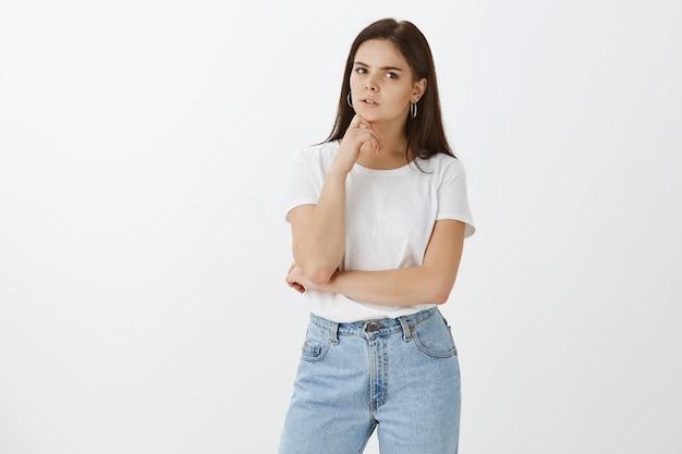 Portret van onzekere jonge vrouw poseren tegen witte muur