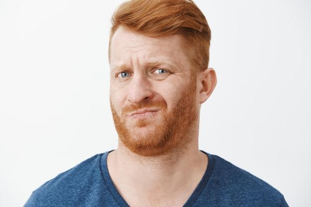Portret van onzekere ontevreden grappige roodharige met cool kapsel, fronsend, grijnzend en rimpelige neus door afkeer