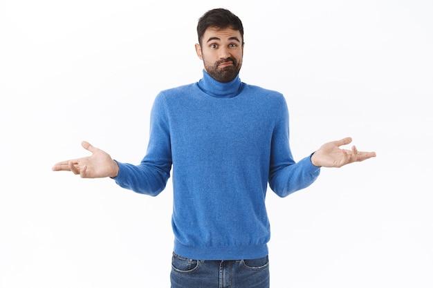 Portret van onzekere, verbijsterde bebaarde man in coltrui, grijns besluiteloos, schouderophalend en spreid handen zijwaarts, weet niet wat doen, geen idee, staande geen idee en verbaasde witte muur