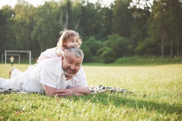 Portret van opa met kleindochter, ontspannen samen in het park