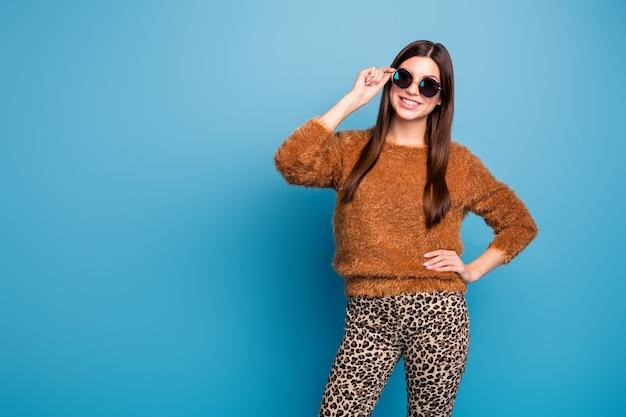 Portret van openhartig mooi mooi meisje geniet van vrije tijd in de herfst, raak haar bril aan, draag stijlvolle kleding die over blauwe kleurmuur wordt geïsoleerd