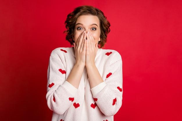 Portret van openhartig mooi schattig meisje minnaar kruis handen dragen stijlvolle trendy trui geïsoleerd op rode muur