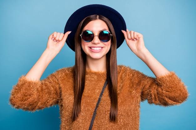 Portret van openhartige inhoud jeugd meisje veel plezier wintervakantie reis touch stijlvolle hoed draag goede kleding geïsoleerd over blauwe kleur muur