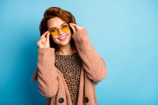 Portret van openhartige mooie mooie vrouw raakt haar moderne stijlvolle zonnebril