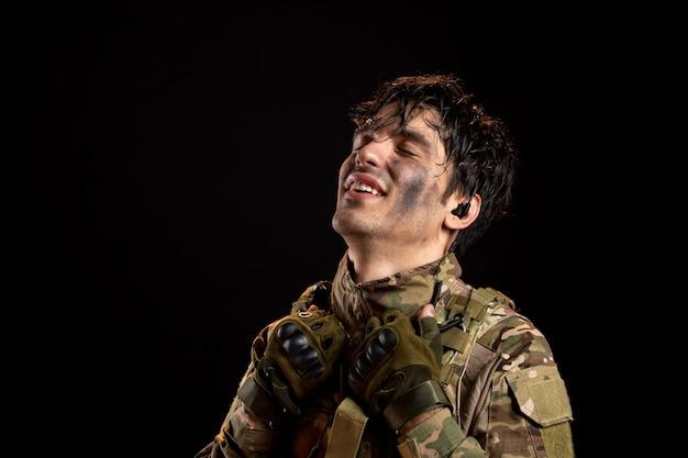 Portret van opgeluchte jonge soldaat in uniform op donkere muur