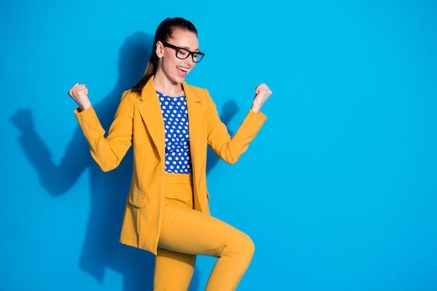 Portret van opgetogen gekke uitvoerende econoom meisje win gelukkige deal partners inkomsten verhogen vuisten schreeuwen ja draag gele jas broek geïsoleerd over blauwe kleur achtergrond