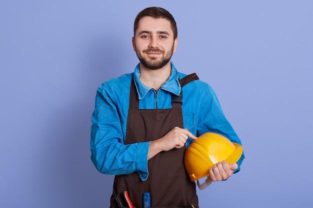 Portret van opgetogen hardwerkende blije jonge man, met gele helm in één hand, gekleed in een blauwe overall en bruine schort, poseren geïsoleerd over blauwe muur in de studio.