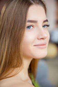 Portret van opgetogen jonge blanke vrouw lachend.