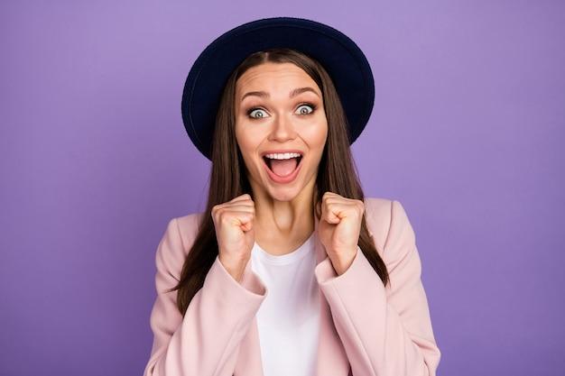 Portret van opgetogen verbaasd meisje onder de indruk van ongelooflijk cadeau aanwezig schreeuw wow omg vuisten op te heffen dragen goed uitziende outfit geïsoleerd over paarse kleur achtergrond