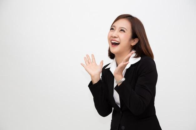 Portret van opgewekte gillende jonge aziatische onderneemster die zich in bedrijfs formeel kostuum bevinden dat over wit wordt geïsoleerd