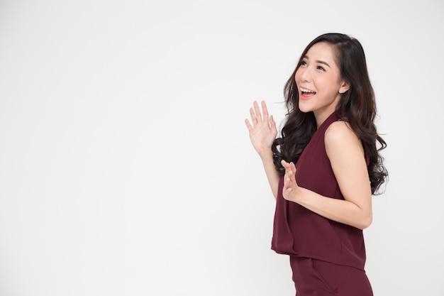 Portret van opgewekte gillende jonge aziatische vrouw die zich in rode kleding bevindt die op wit wordt geïsoleerd