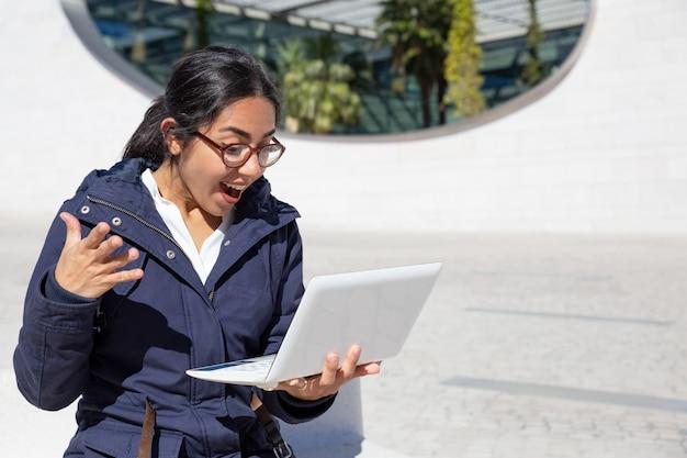 Portret van opgewekte jonge vrouw die laptop in openlucht met behulp van