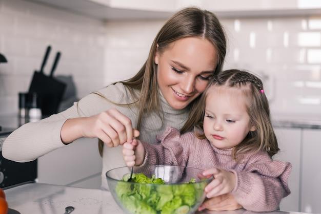 Portret van opgewekte vrouw die gekookte gezonde voedselsalade met haar dochtertje eet
