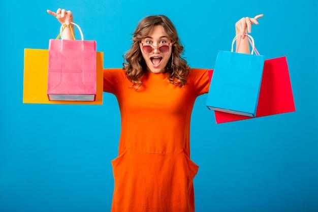Portret van opgewonden aantrekkelijke glimlachende stijlvolle vrouw shopaholic in oranje trendy jurk met boodschappentassen op blauwe studio achtergrond geïsoleerd
