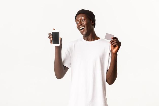 Portret van opgewonden aantrekkelijke jonge afro-amerikaanse man in beanie, vreugde terwijl creditcard met gsm-scherm wordt weergegeven