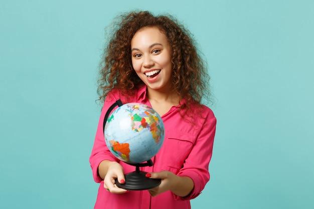 Portret van opgewonden afrikaans meisje in casual kleding in handen earth wereldbol geïsoleerd op blauwe turkooizen achtergrond in studio. mensen oprechte emoties, lifestyle concept. bespotten kopie ruimte.