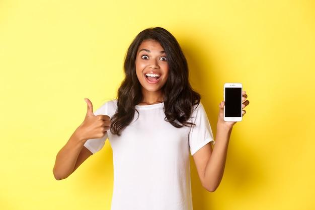 Portret van opgewonden afro-amerikaans meisje dat smartphonescherm toont en thumbsup maakt die ...
