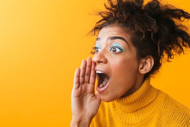 Portret van opgewonden afro-amerikaanse vrouw met afro kapsel schreeuwen of bellen terwijl staande, geïsoleerd