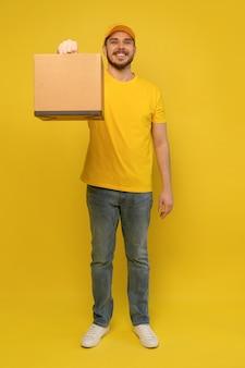 Portret van opgewonden bezorger in geel uniform met papieren doos geïsoleerd over gele muur