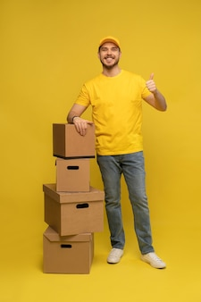 Portret van opgewonden bezorger in geel uniform met papieren doos geïsoleerd over gele muur Premium Foto