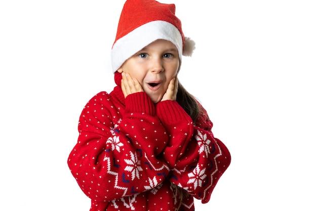 Portret van opgewonden charmant meisje in rode kerstmuts in rode kersttrui met rendieraanraking...