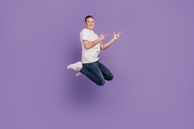 Portret van opgewonden dromerige positieve man springt directe vingers lege ruimte op violette achtergrond