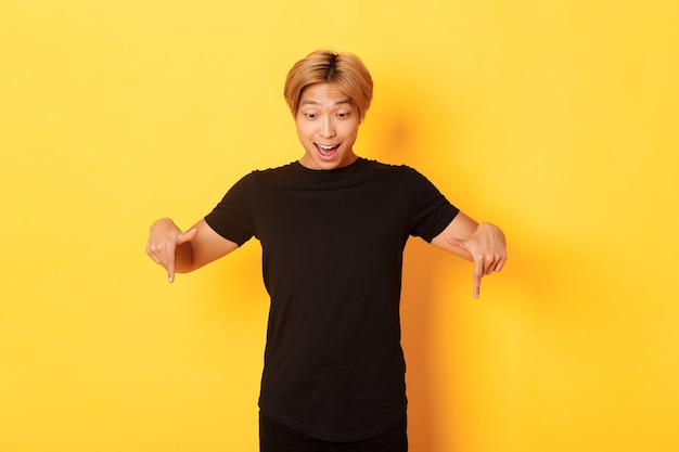 Portret van opgewonden en gelukkig aziatische man met blond kapsel