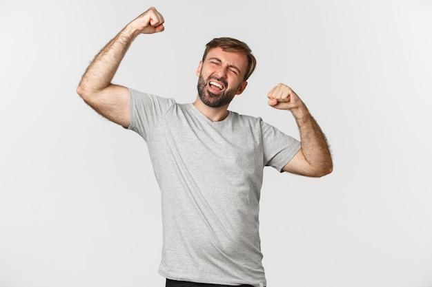 Portret van opgewonden en gelukkig man in grijs t-shirt, vuist pomp maken en ja schreeuwen tegen vieren