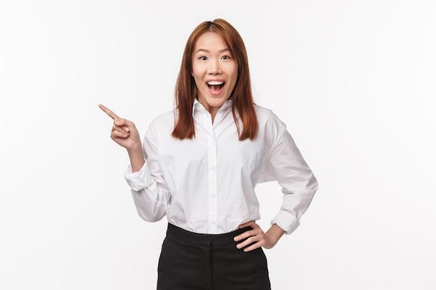 Portret van opgewonden en gelukkige dromerige aziatische vrouw in wit overhemd, zwarte rok, camera met open mond gefascineerde blik, wijzende vinger naar links naar geweldig cool nieuw product, wil het proberen,
